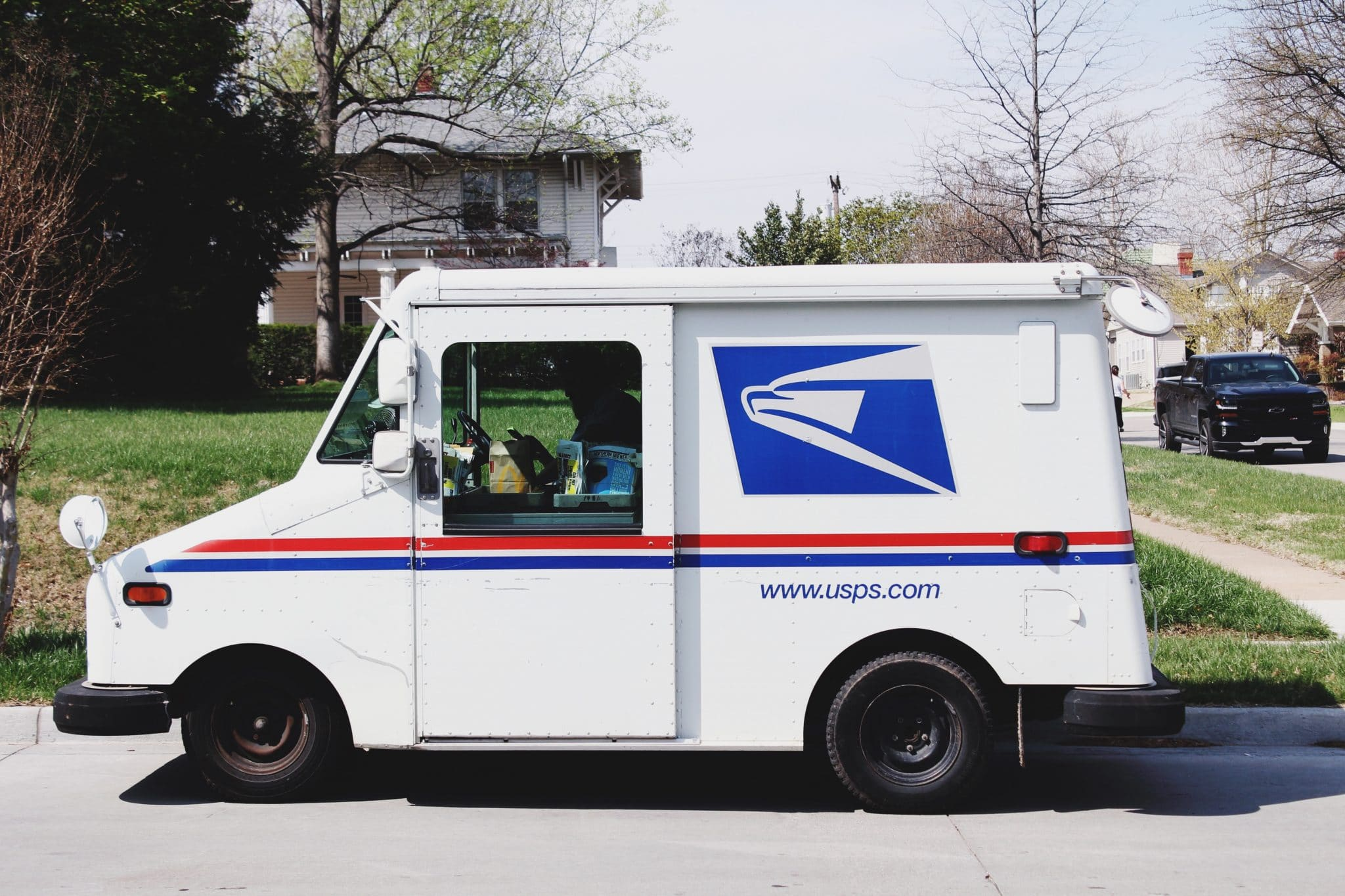 A United States Postal Service truck sitting outside on a suspiciously delightful day.