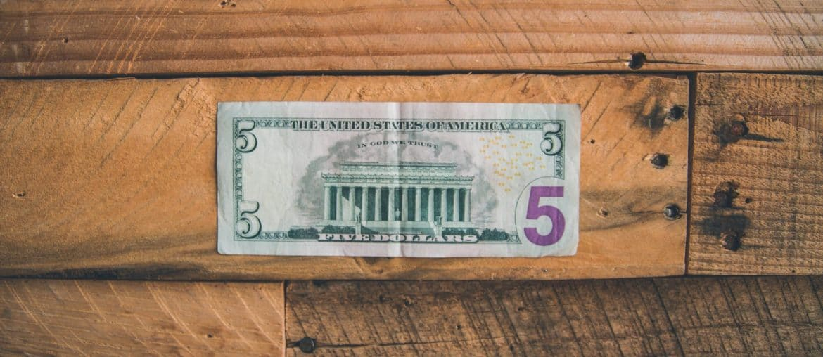 An all American $5 bill sitting on a wooden table.