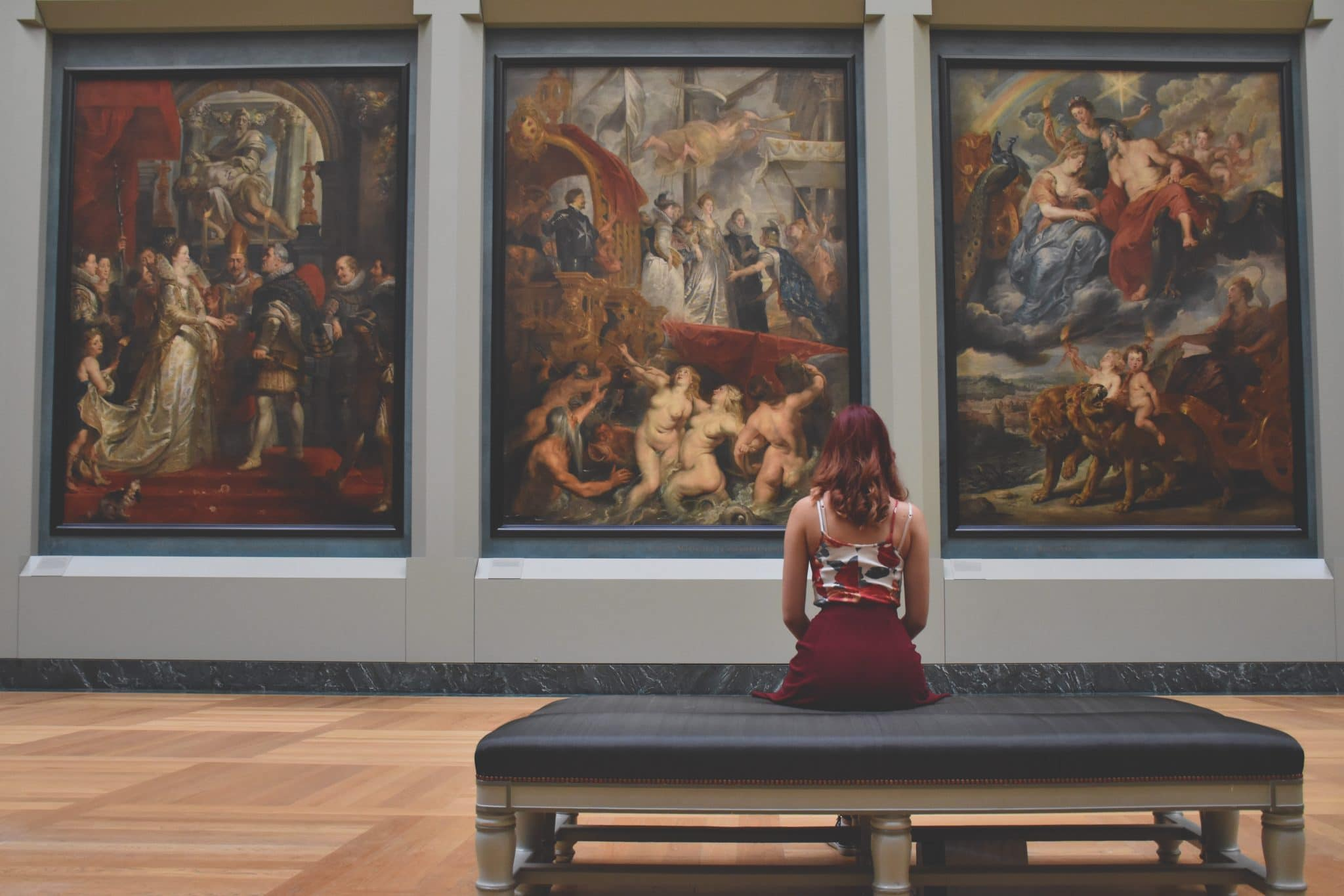Woman sits in an art gallery looking at some really famous paintings