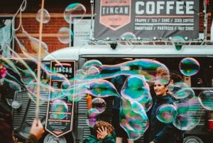 Students having fun making bubbles outside of a coffee shop