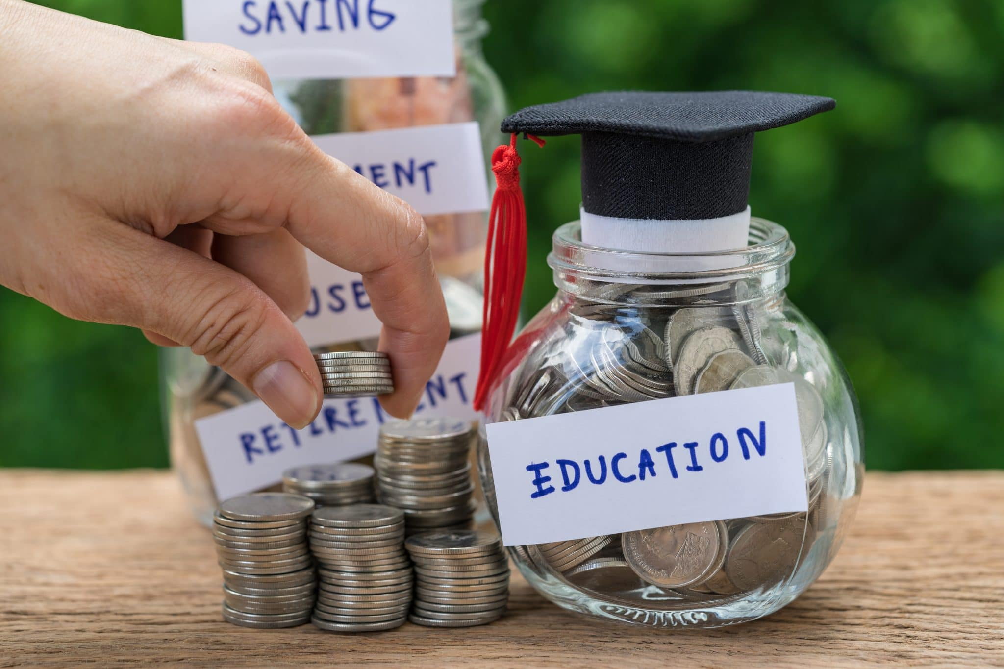 Woman hand holding stack of coins money and glass jar with full of coins and graduates hat label as Education, education or savings concept.