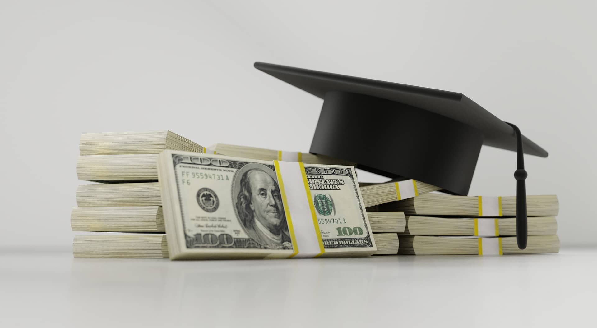 stack of money with graduation cap.