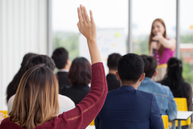 adult student raising hand in college classroom
