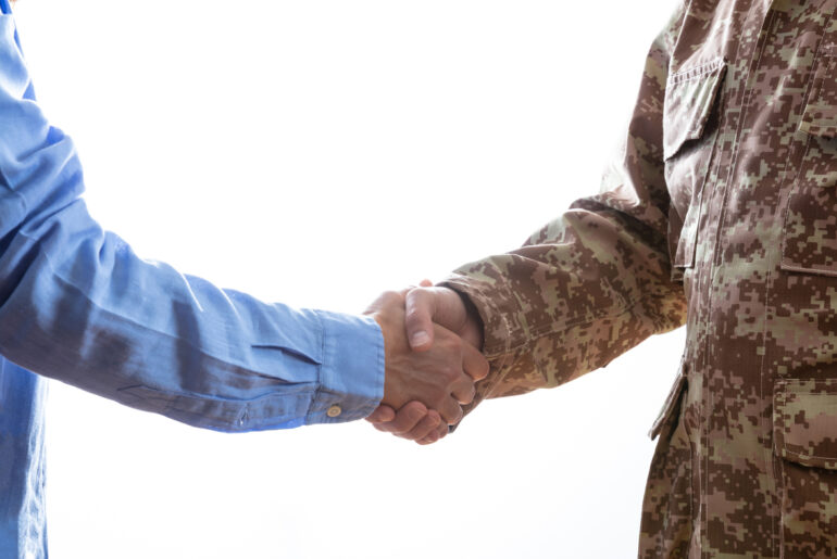 former military member shaking hands with civilian